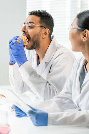 Gloved young male worker of food control biting hamburger or cheeseburger in lab