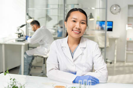 Young successful Asian female researcher in whitecoat and gloves looking at you