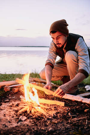 Serious young bearded hiker in cap putting wood while setting fire near coastline at sunset