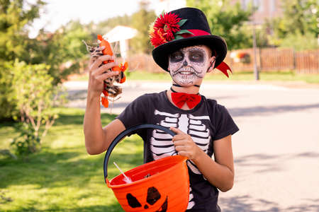 Cheerful boy with painted face in halloween t-shirt and hat boastin with treats