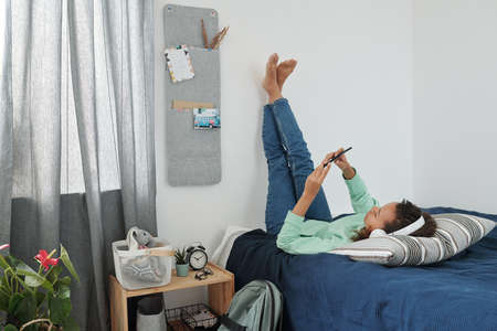 Relaxed mixed-race girl in headphones and casualwear using smartphone on bed