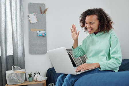 Young cheerful mixed-race woman waving hand to her friend on laptop display 版權商用圖片