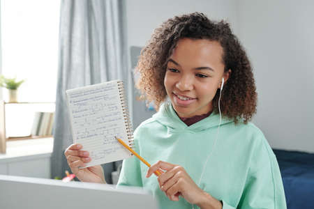 Smiling mixed-race teenage girl with earphone pointing at notes in copybook