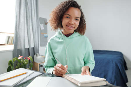 Cheerful mixed-race teenage student making notes in copybook in bedroom 版權商用圖片