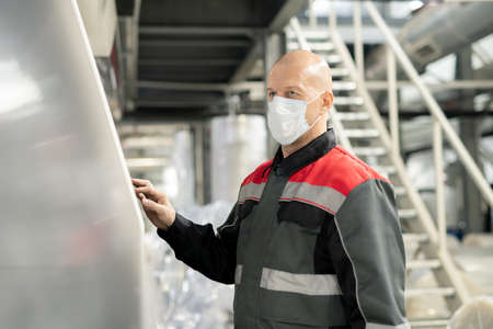 Bald mature worker of contemporary large polymer processing factory