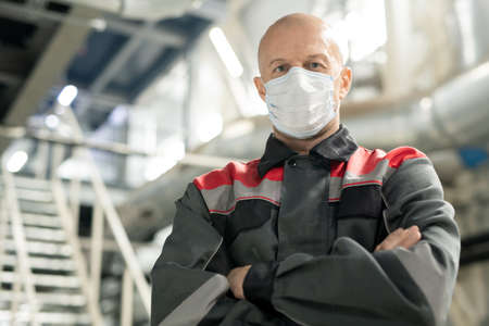Bald mature worker in uniform and protective mask standing against staircase