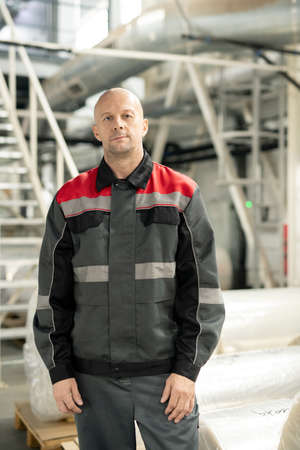 Bald mature male engineer in workwear standing inside polymer processing factory
