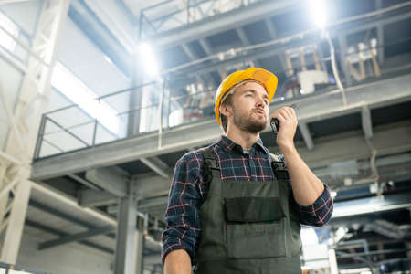 Young confident engineer in protective helmet and workwear using walkie talkie Banco de Imagens