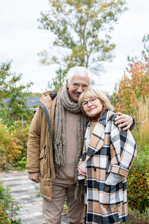 Happy affectionate senior man in warm casualwear standing by his blond wife