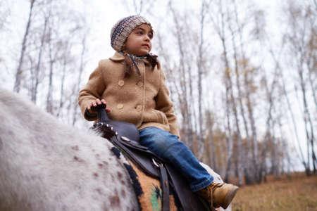 Cute Little Girl Sitting On Pony Foto de archivo