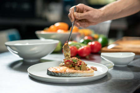 Hand of young male chef putting roasted vegetables on piece of fried salmon