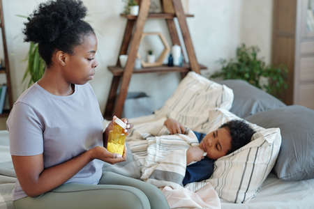 Young careful mother holding bottle with pills while sitting by sick little son