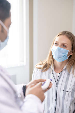 Young female patient in mask looking at her doctor during medical consultation