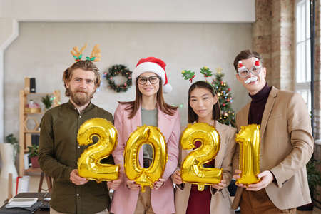 Young white collar workers in xmas accessories holding numbers of next year