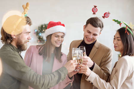 Young cheerful colleagues in xmas headbands clinking with flutes of champagne