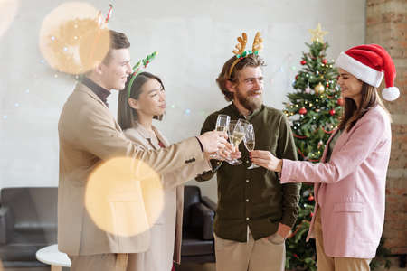Happy young elegant colleagues in xmas headbands looking at Santa female