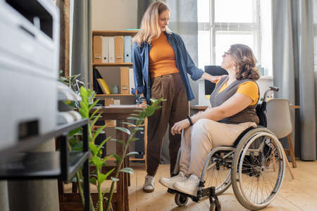 Young blond woman in casualwear looking at her disable friend in wheelchair