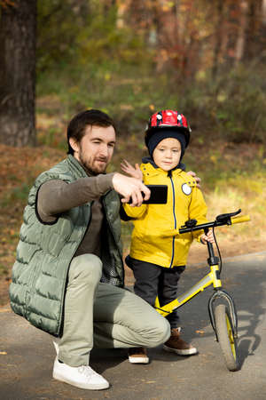 Young father with smartphone making selfie with his cute little son waving hand