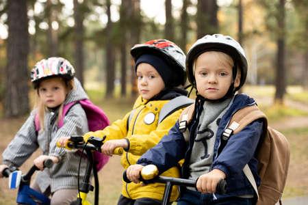 Group of cute little kids in protective helmets sitting on their balance bikes 版權商用圖片