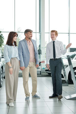 Male manager of modern auto center presenting one of new cars to happy couple