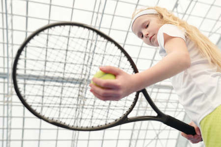 Serious youthful blond girl in white activewear holding tennis ball under racket