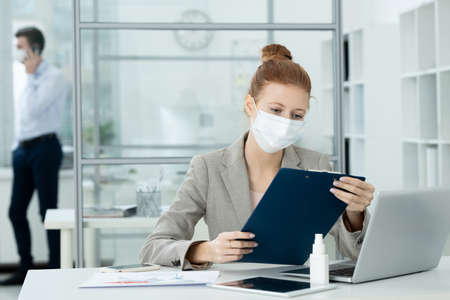 Young serious businesswoman in protective mask looking at financial document