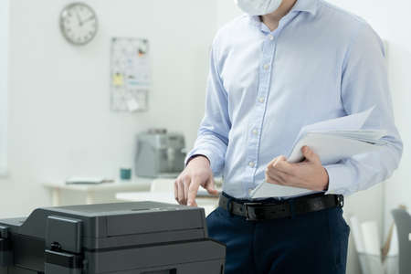 Young businessman in formalwear and protective mask making copies of papers