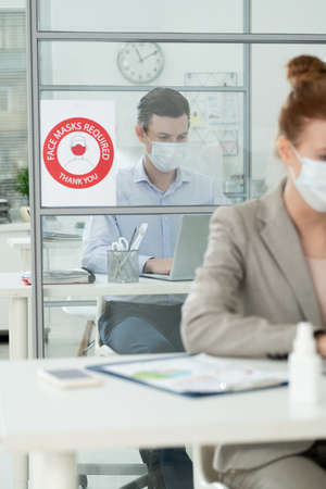Young businessman in protective mask and formalwear looking at laptop display