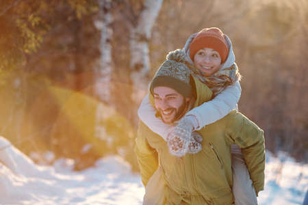 Cheerful guy in winterwear giving his girlfriend piggyback while chilling out