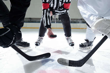 Hockey referee with puck standing on rink with two rivals on his right and left