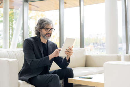Mature bearded broker in formalwear and eyeglasses looking through online news