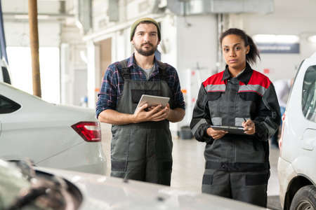 Two young serious workers of car maintenance center standing between automobiles