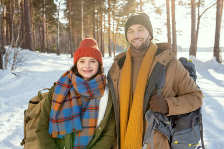 Young smiling couple in winterwear standing in front of camera in the forest