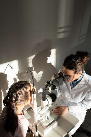 Female ophthalmologist in whitecoat checking eyesight of little girl in clinics