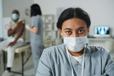 Young serious mixed-race female clinician in uniform and protective mask