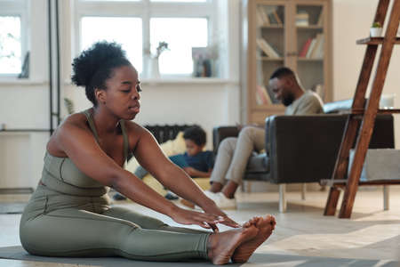 Fit young African woman in tracksuit sitting on the floor of living-room during physical exercise