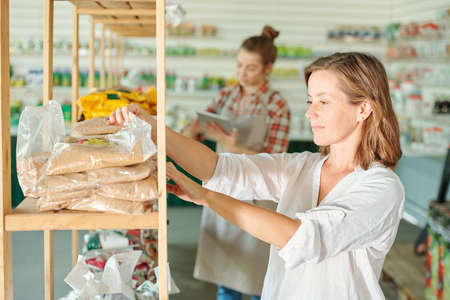 Pretty brunette woman in casualwear and eyeglasses standing by shelf with packed fertilizers and choosing one for her garden in supermarket