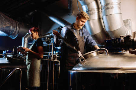 Young woman in workwear using digital tablet while her male colleague opening lid of huge steel cistern during process of beer production