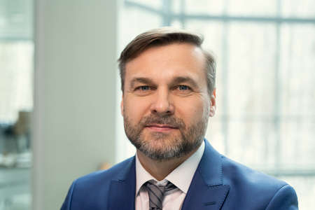 Portrait of smiling handsome middle-aged businessman with stubble standing in contemporary office Foto de archivo