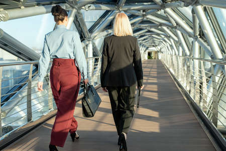rear view of contemporary businesswomen walking along modern building