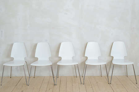 Row of white plastic chairs on metal legs placed on parquet against gray wall