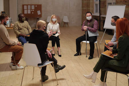 Group of people in trouble interacting with one another and counselor during session Фото со стока