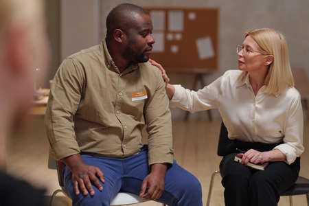 Blond mature female comforting African male patient at session