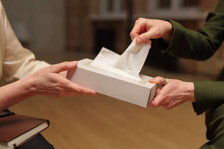 Young female taking paper handkerchief out of box held by psychologist