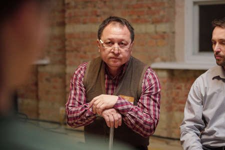 Aged man in eyeglasses and casualwear describing his problem at psychological session