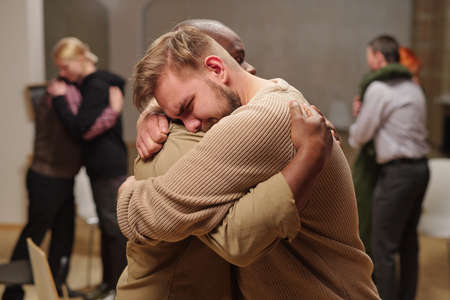 Two young intercultural man embracing while one of them crying