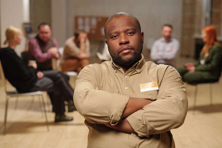 Serious African man crossing arms by chest against group of people discussing thrir problems Фото со стока