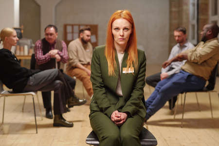 Troubled female in green suit sitting in front of camera during session