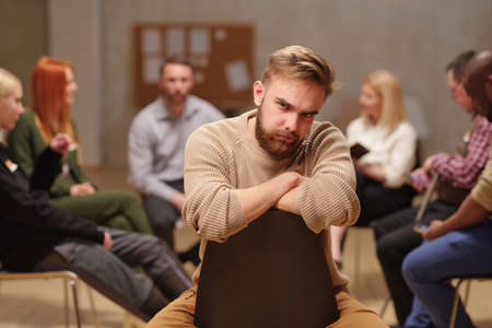 Frowning guy with beard sitting on chair during psychological session