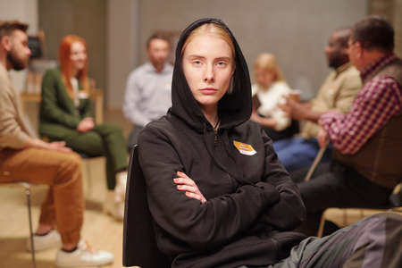 Serious girl with her arms crossed by chest attending psychological course